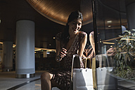 Smiling woman sitting looking into shopping bag - MRAF00184