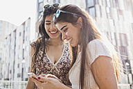 Two happy young women looking at cell phone in the city - MRAF00187