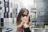 Two happy young women hugging in the city - MRAF00190