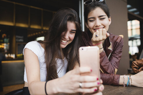 Two happy young women looking at cell phone in a bar - MRAF00202
