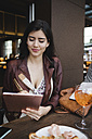Woman using tablet in a bar - MRAF00205