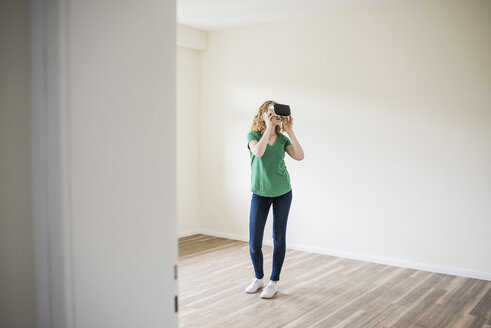 Woman in empty apartment wearing VR glasses - UUF10694