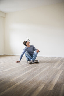 Man in empty apartment wearing VR glasses - UUF10697