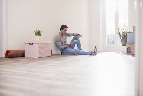 Young man in new home sitting on floor with tablet - UUF10700