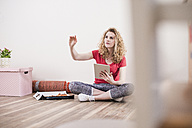 Young woman in new home sitting on floor with tablet - UUF10703