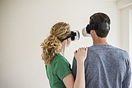 Young couple in empty apartment wearing VR glasses - UUF10706