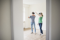 Young couple discussing in empty apartment wearing VR glasses - UUF10709