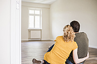 Young couple in new home sitting on floor - UUF10712