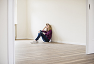 Young woman in new home sitting on floor - UUF10715