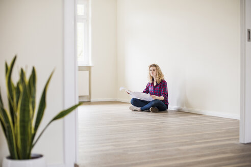 Young woman in new home sitting on floor with plan - UUF10718