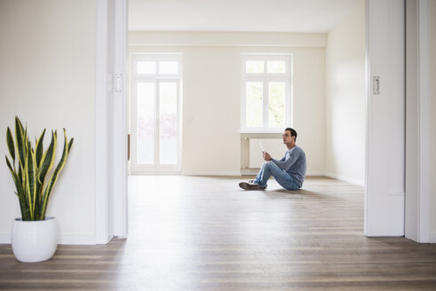 Young man in new home sitting on floor with tablet - UUF10724