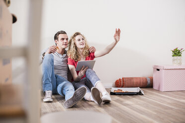 Young couple in new home sitting on floor with tablet - UUF10730