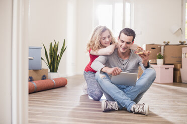 Young couple in new home sitting on floor with tablet - UUF10733