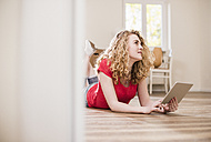 Young woman in new home lying on floor with tablet - UUF10736