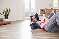 Happy young couple in new home lying on floor with tablet - UUF10739