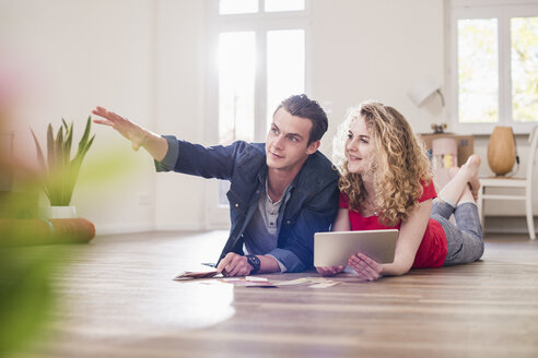 Young couple in new home lying on floor with tablet choosing from color sample - UUF10742