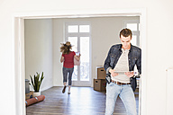 Young man in new home using tablet with woman in background carrying cardboard box - UUF10745