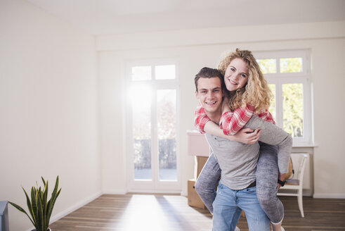 Portrait of happy young couple in new home - UUF10748