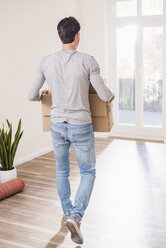 Young man carrying cardboard box in new home - UUF10754