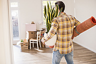 Young man carrying belongings in new home - UUF10757