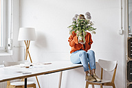 Young woman sitting on table holding flower vase in front of her face - KNSF01459