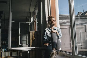 Young woman with tablet looking out of window - KNSF01474