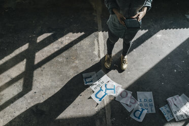 Woman standing on concrete floor using tablet and working on letter templates - KNSF01480