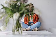 Young woman sitting on table using tablet covered by flowers - KNSF01513
