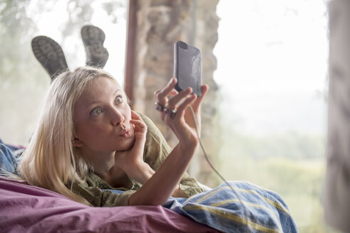 Portrait of young woman lying on bed taking selfie with cell phone - ZOCF00409