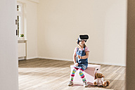 Girl in empty apartment wearing VR glasses - UUF10768