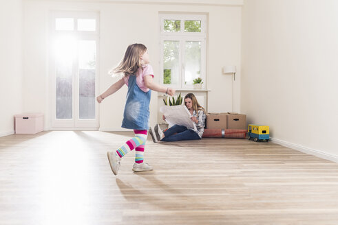 Happy girl running in empty apartment with mother reading plan - UUF10771