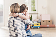 Mother and daughter hugging in empty apartment - UUF10774