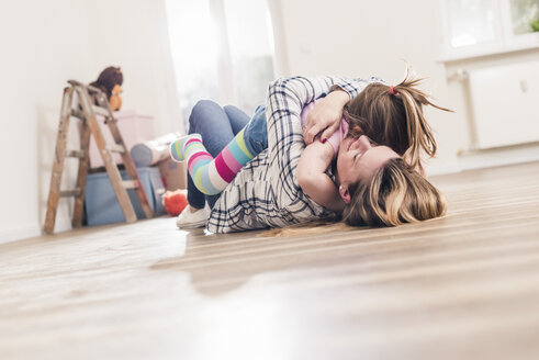 Mother and daughter hugging on the floor in new home - UUF10780