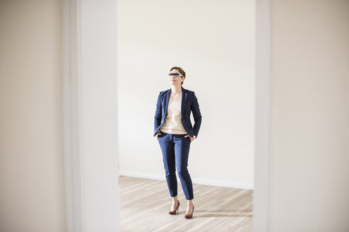 Woman in empty apartment wearing smartglasses - UUF10798