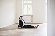 Woman in empty apartment wearing VR glasses - UUF10801