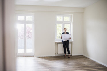 Woman in empty apartment with plan - UUF10804