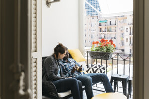 Two young professionals on office balcony, using their smartphones - JRFF01364
