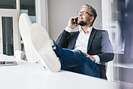 Businessman sitting phoning in office with feet on desk - JOSF01016