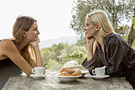 Two friends smiling at each other at breakfast table - ZOCF00448