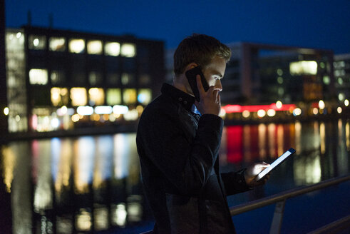 Young man on the phone looking at tablet at night - JOSF01047