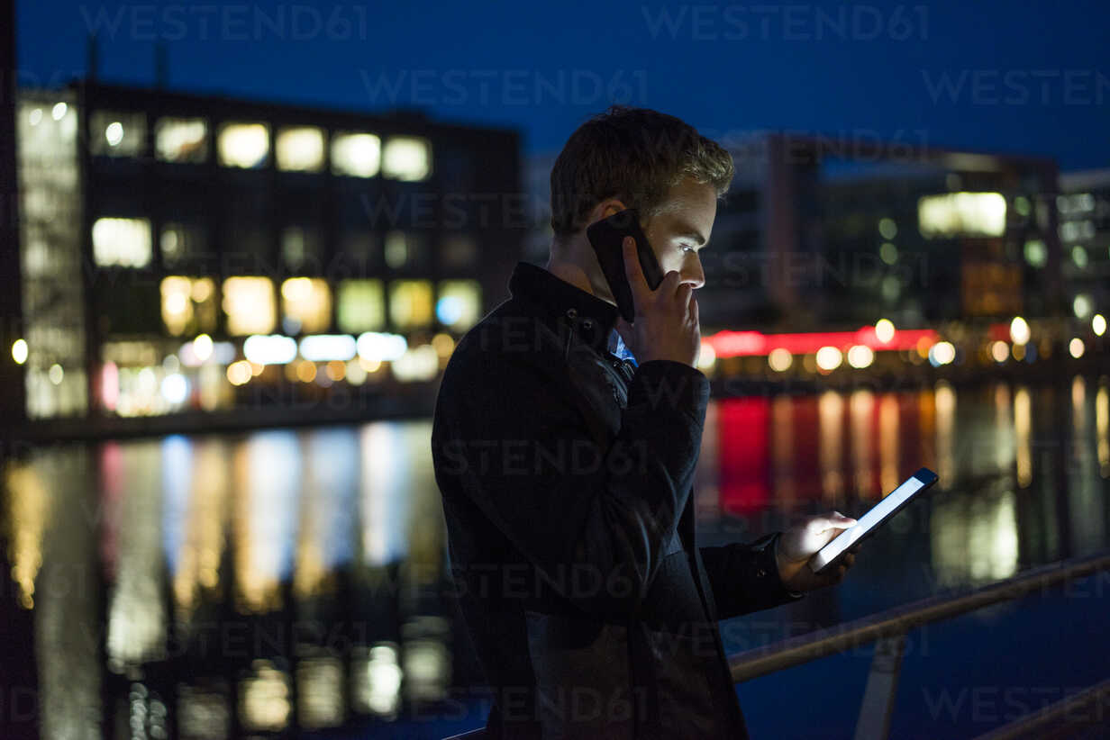 Young man on the phone looking at tablet at night - JOSF01047 - Joseffson/Westend61