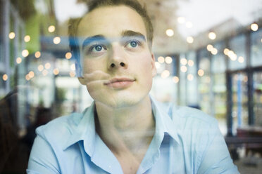 Daydreaming young man behind windowpane - JOSF01053