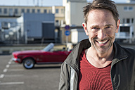 Portrait of smiling mature man in front of his sports car on parking level - FMKF04150