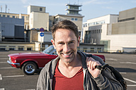 Portrait of smiling mature man in front of his sports car on parking level - FMKF04159