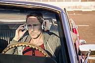 Portrait of mature man sitting in his sports car listening music with head phones - FMKF04162