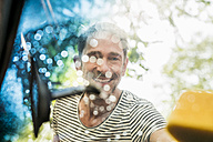 Portrait of smiling mature man washing windscreen of his car - FMKF04171