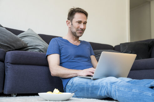 Portrait of smiling man sitting on the floor in the living room using laptop - FMKF04177