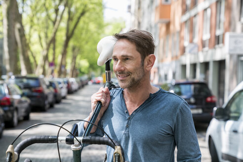 Portrait of mature man carrying his bicycle on the shoulder - FMKF04186