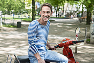Portrait of smiling mature man with motor scooter - FMKF04192
