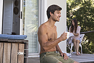 Man sitting on terrace with cup of coffee and woman in background - WESTF23167